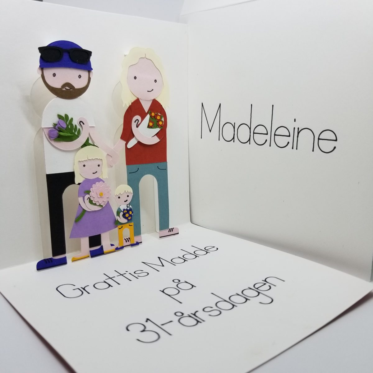 Paper cut out illustration of family as a pop-up birthday greeting card.
